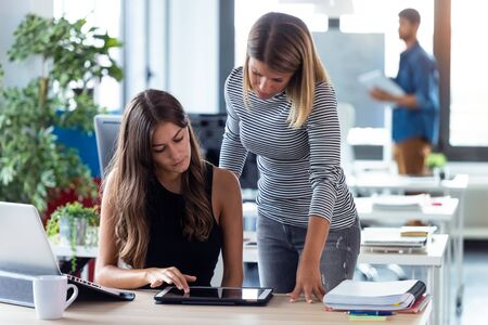 Shot of two business young women working together with digital tablet in the modern startup office.