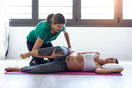 Shot of physiotherapist helping to beautiful pregnant woman for doing pilates exercises preparing for childbirth.