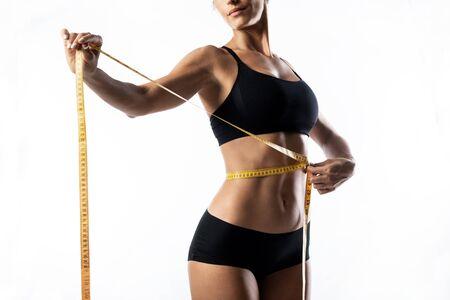 Primer plano de mujer midiendo su cuerpo delgado aislado sobre fondo blanco.