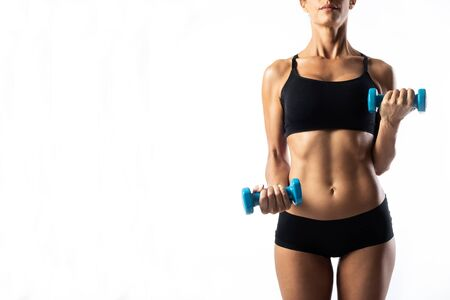 Close-up of a young woman lifting blue dumbbells over white background.