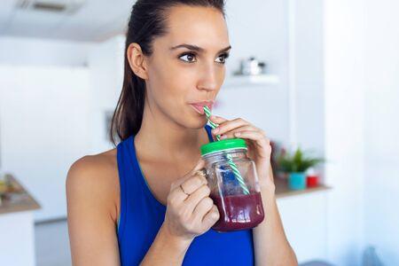 Photo d'une belle jeune femme sportive buvant du jus de désintoxication dans la cuisine à la maison.