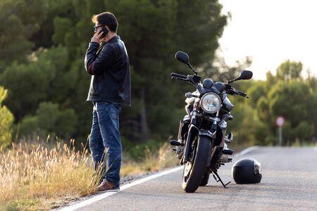 Foto de motociclista hombre hablando por teléfono con el seguro de su motocicleta después de haber sufrido una avería en la carretera.