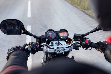 Close-up of back view of driver riding motorcycle on the asphalt road.