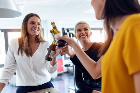 Shot of three young entrepreneur women toasting with a bottle of beer to celebrate a success in the office.