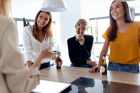Shot of team of young entrepreneur women celebrating a success while drinking beer in the office.