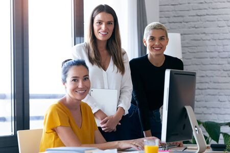 Portrait of modern three entrepreneur women looking at camera while working in the office.