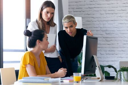Shot of three modern businesswomen talking and reviewing the latest work done on the computer in a joint workspace