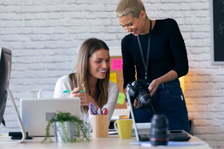 Shot of smiling entrepreneur women reviewing last photographs in the camera for they next work in the office.