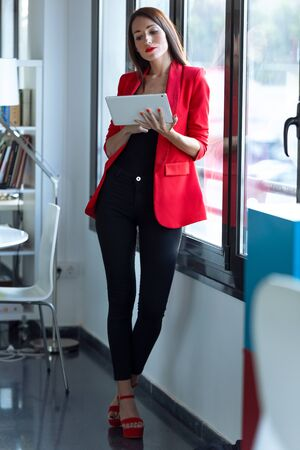 Shot of pretty young businesswoman using her digital tablet while standing next to the window in the office. Zdjęcie Seryjne