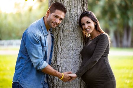 Portrait of pretty pregnant couple looking at the camera while holding hands in the park.
