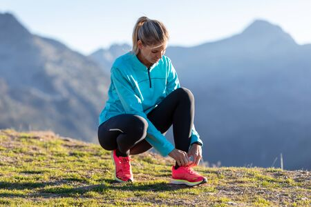 Shot of trail runner woman tying laces on running shoes before doing workout on mountains.
