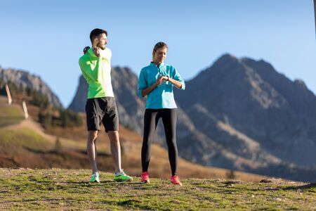 Shot of healthy young man doing stretching exercises while his girlfriend use her smartwatch on the mountain.
