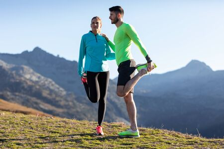 Shot of healthy young couple doing stretching exercises together on mountain trail in the morning.