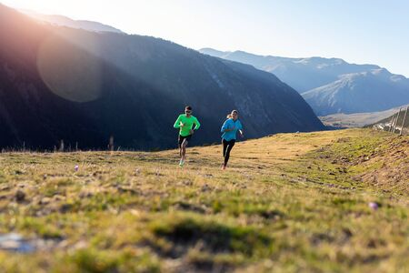 Shot of healthy young couple running on mountain trail in the morning. Zdjęcie Seryjne