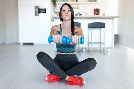 Shot of beautiful young woman lifting dumbbells while sitting on the floor at home. 스톡 콘텐츠