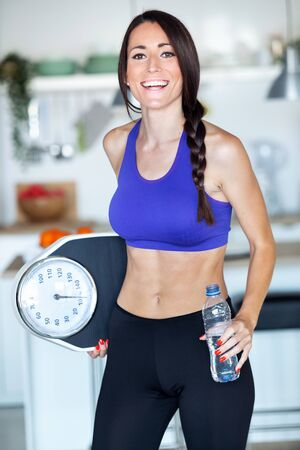 Shot of happiness young woman looking at camera and posing with weigh scale at home. Zdjęcie Seryjne