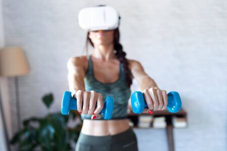 Shot of beautiful young woman doing a workout with dumbbells with virtual reality headset at home. Zdjęcie Seryjne