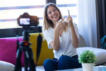 Shot of pretty young woman blogger holding beauty products and smiling while making social media video