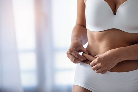 Close-up of young woman catching fat on the stomach to see how she reduced belly at home. Stockfoto