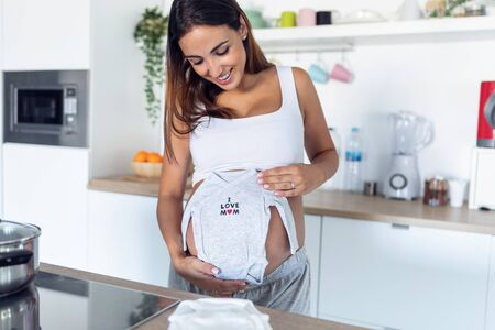 Shot of pretty young pregnant woman smiling while holding baby clothes on belly in the kitchen at home. Stock Photo