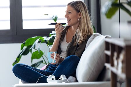 Shot of pretty young woman talking on mobile phone with hands free while drinking cup of coffee on sofa at home.