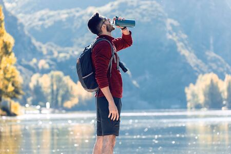 Hiker young man traveler with backpack drinking water while standing in front of lake. Zdjęcie Seryjne