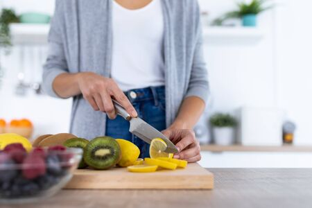 Close-up of womans hands while she cutting lemon over wooden table in the kitchen.