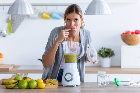 Shot of pretty young woman tasting the detox juice she just made with the blender at home.