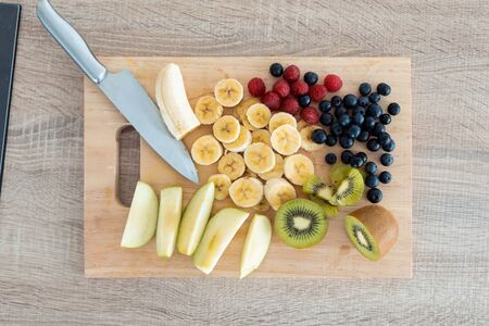 Shot of different pieces of fresh fruits on a wooden board for cutting. Healthy food concept.