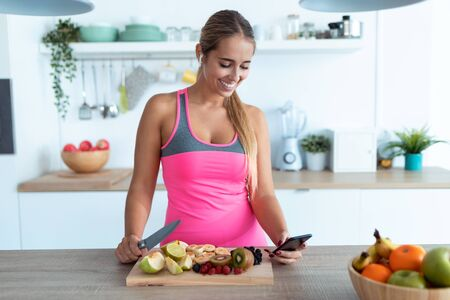 Shot of pretty young woman using her mobile phone while preparing detox juice in the kitchen at home. Zdjęcie Seryjne