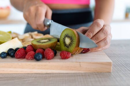 Close-up of womans hands cutting kiwi on a wooden table.