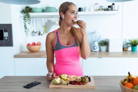 Aufnahme einer hübschen jungen Frau, die ein Stück Apfel isst, während sie zu Hause Musik in der Küche hört. Standard-Bild