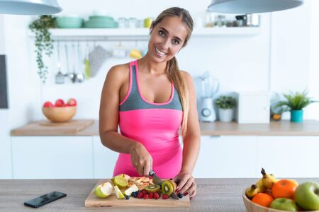 Shot of pretty young woman looking at camera while cutting kiwi in the kitchen at home. Zdjęcie Seryjne