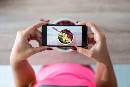 Close-up of womans hands holding mobile phone while taking photograph to bowl with fresh fruit.