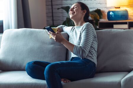 Shot of smiling young woman using her mobile phone while sitting on sofa in the living room at home.