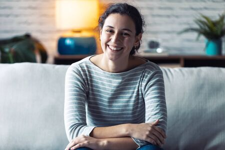 Portrait of smiling young woman looking at camera while sitting on sofa in the living room at home.
