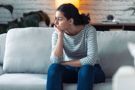 Shot of boring young woman looking to side and thinking while sitting on the sofa at home. Zdjęcie Seryjne