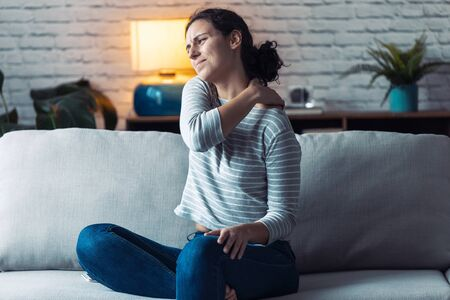 Shot of young woman with back pain sitting on the sofa in the living room at home.
