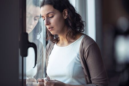 Shot of sad young woman crying while looking through the window at home. Zdjęcie Seryjne