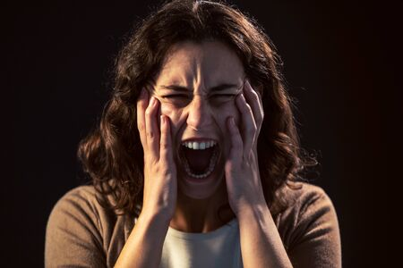Photo of a young woman close-up screaming on black background. Mental illness concept. Zdjęcie Seryjne