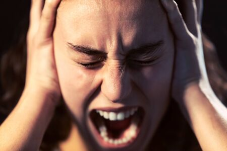 Photo of a young woman close-up screaming on black background. Mental illness concept. Stock Photo - 136303968