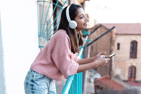 Shot of pretty young woman listening to music with smartphone while standing on the rooftop at home.