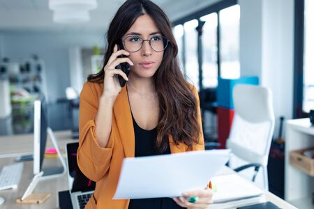 Shot of business young woman talking on mobile phone while holding papers in the office.