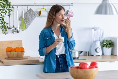 Shot of pretty young woman eating yogurt while standing in the kitchen at home.