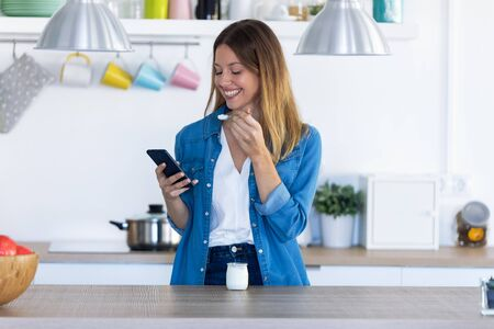 Shot of pretty young woman using her mobile phone while eating yogurt in the kitchen at home. Zdjęcie Seryjne