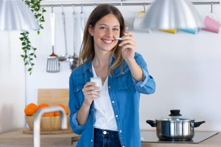 Shot of pretty young woman looking at camera while eating yogurt in the kitchen at home.