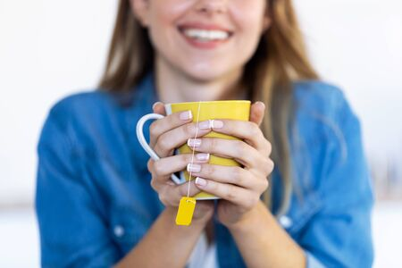 Close-up of pretty young woman holding a cup of tea in the kitchen at home.