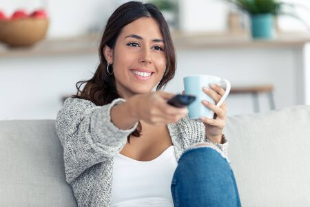Shot of pretty young woman turning on the tv while drink coffee on sofa at home.