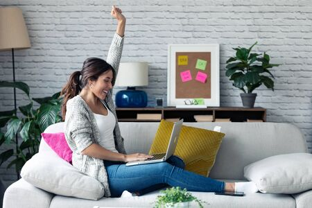 Shot of pretty young woman celebrating something while using her laptop on sofa at home.
