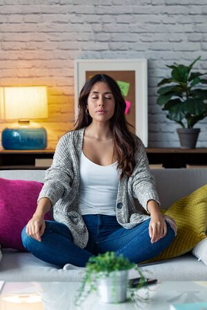 Shot of pretty young woman in lotus position sitting on sofa while relaxing at home. Zdjęcie Seryjne